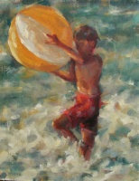 Young boy in the ocean up to his knees holding a yeloow and white beach ball over his head