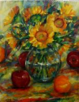 Apples around the base of a clear vase with sunflowers. Yellow, red, green and blue colors