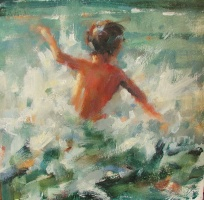 The back of a young boy playing in the waves of the light green ocean